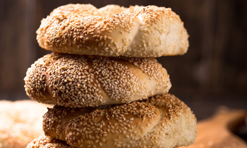 Greek koulouri or Turkish bagels called Simit in stack. Traditional street food, crispy sesame bread ring bagels