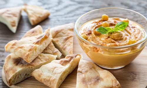 Bowl of hummus with pita slices