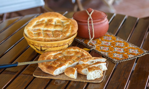 Ramadan pide cut and outdoor served with rasary, breadbasket  and pottery. photo with shallow depth of field