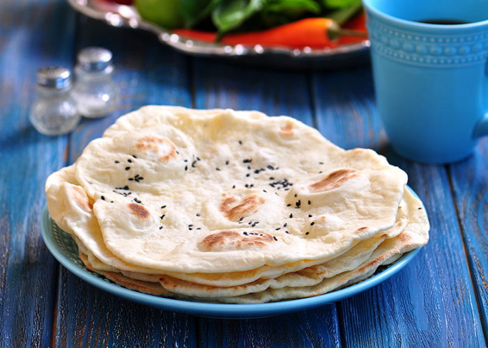 Homemade bread pita bread on a blue background.