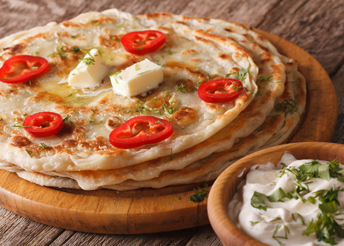 Indian food: hot paratha with butter close-up on the table. Horizontal
